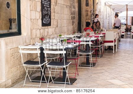 DUBROVNIK, CROATIA - MAY 28, 2014: Guests sitting at restaurant street terrace.