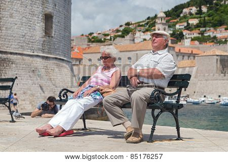 DUBROVNIK, CROATIA - MAY 27, 2014: Elderly couple  sitting on bench on dock in front of the St. John fortress near the old port. Fortress houses the Maritime Museum and the aquarium.