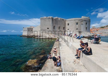 DUBROVNIK, CROATIA - MAY 27, 2014: Tourists sitting on bench and stairs on dock in front of the St. John fortress near the old port. Fortress houses the Maritime Museum and the aquarium.