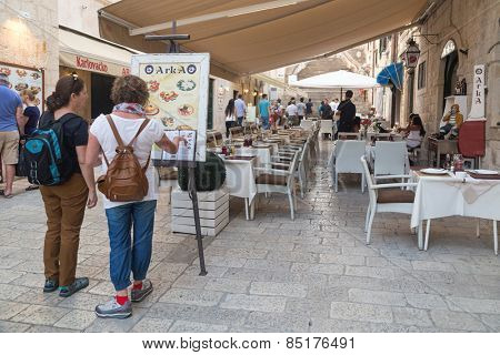 DUBROVNIK, CROATIA - MAY 28, 2014: Tourists looking at menu in front of the restaurant terrace. Dubrovnik has many restaurants which offer traditional Dalmatian cuisine and some great wine lists.