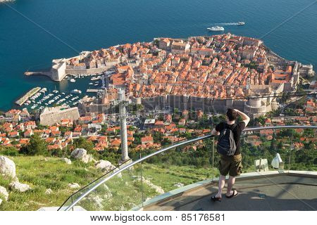 DUBROVNIK, CROATIA - MAY 26, 2014: Tourist at viewpoint at cable car station connecting Ploce and mountain Srdj above town where you can enjoy a panoramic view of Old Town and the surrounding islands.
