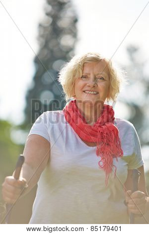 Senior woman walking with hiking sticks in summer in nature