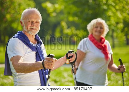 Happy senior couple hiking together in summer in nature