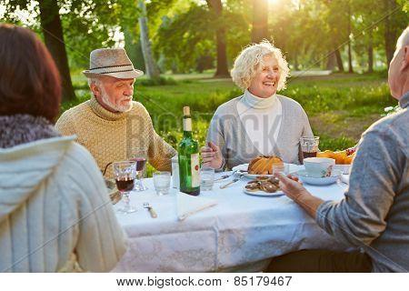 Happy family with seniors celebrating birthday in a garden in summer