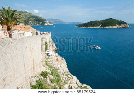 DUBROVNIK, CROATIA - MAY 26, 2014: Old city walls and Lokrum island. Old wall is one of Dubrovnik's most famous feature. It is almost 2 km long.