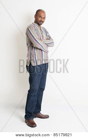 Full body Asian Indian guy in casual wear crossed arms standing on plain background with shadow.