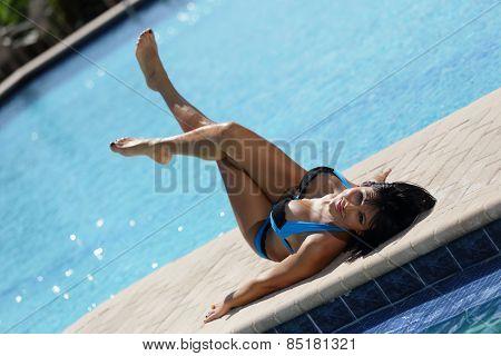 Woman sunbathing by the pool
