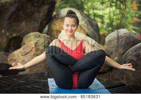 Woman practicing yoga. Fetus Pose. Garbhasana