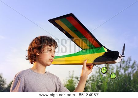 Teen with homemade radio-controlled model aircraft (airplane is hand made not copyright)