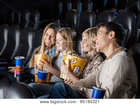 Cheerful family having snacks while enjoying movie in cinema theater