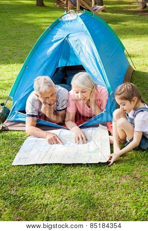 Grandparents with granddaughter studying map at campsite in park