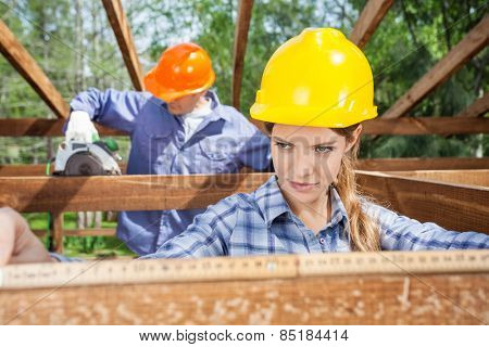 Female architect using measure tape while construction worker working in background at site