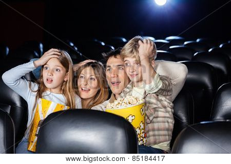Amazed family with hands on heads watching movie in cinema theater
