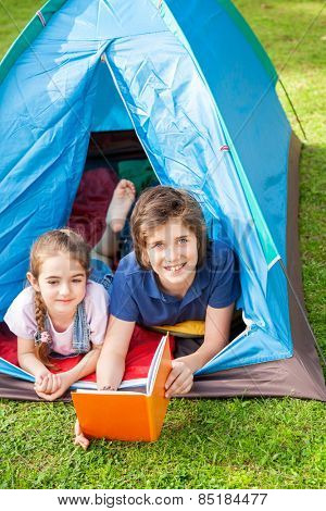 Portrait of happy boy with sister reading book in tent at park