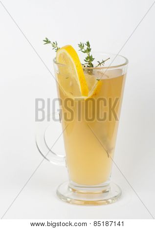 tea glass with thyme lemon on a white