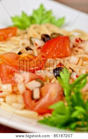 Pasta with tomato, black olives, capers and greens