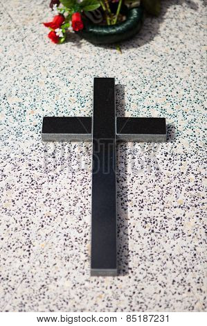 Black cross and wreath on a granite grave.
