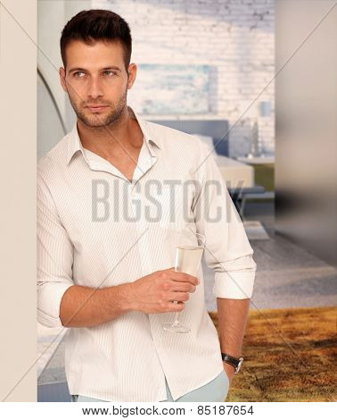 Handsome serious casual caucasian man with a glass of champagne at designer home. Unsmiling, standing against wall, hand in pocket.