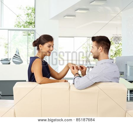 Happy young casual attractive caucasian lady is getting engagement ring from boyfriend at home. Sitting on sofa ring on hand, smiling, proposal, bright home.