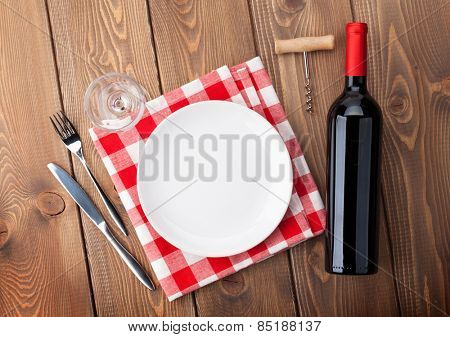 Table setting with empty plate, wine glass and red wine bottle. View from above over rustic wooden table background