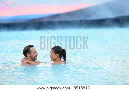 Hot spring geothermal spa on Iceland. Romantic couple in love relaxing in hot pool on Iceland. Young woman and man enjoying bathing relaxed in a blue water lagoon Icelandic tourist attraction. Sunset.