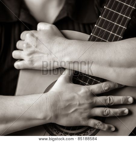 Classic guitar closeup in sepia - Musician hands embracing a classic acoustic guitar
