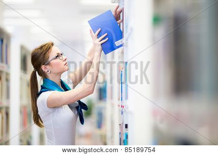 Pretty, female college student in a library, looking for a book (shallow DOF; color toned image)