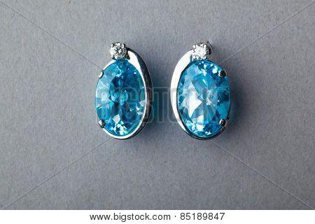 blue sapphire earrings on grey background