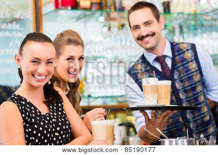 Two woman friends in coffee bar drinking latte macchiato in glass, a barista preparing drinks in the background