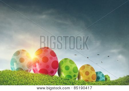 Colorful Easter eggs painted with dots on a grass field