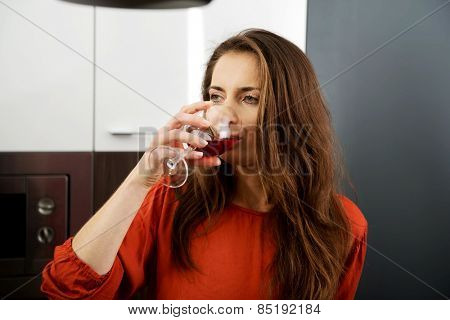 Woman with his wineglass in the kitchen at home.