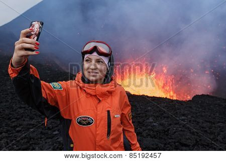 Eruption Tolbachik Volcano On Kamchatka, Girl Photographed Selfie On Background Lava Lake In Crater
