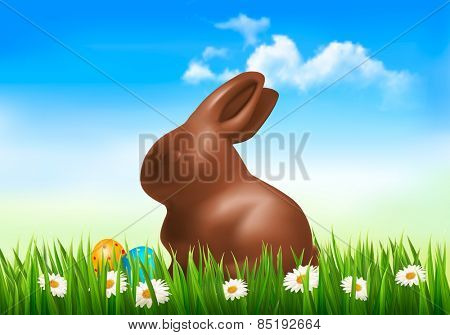 Holiday background with chocolate bunny with easter eggs in grass.
