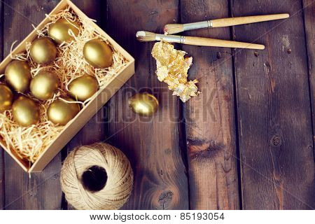Paintbrush and gold leaf with painted Easter eggs
