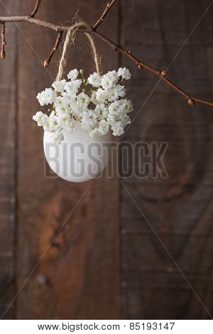 Bunch of of white baby's breath flowers (gypsophila) in egg shell on the brown wooden plank. Shallow depth of field, focus on near flowers. Easter decor
