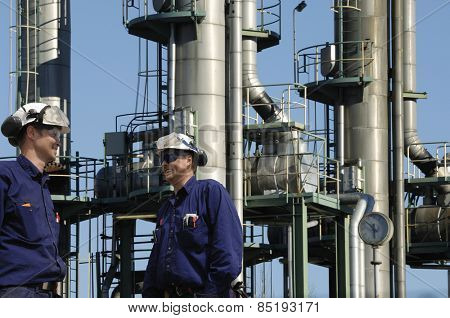 refinery workers with three fuel towers inside industry, refinery detail