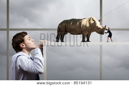 Businessman peeping from under table at woman fighting with massive rhino
