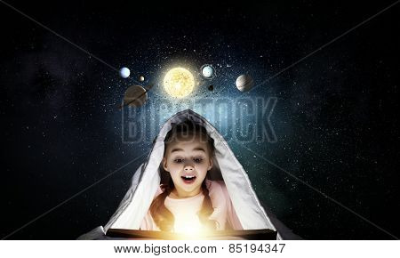 Cute girl of school age with book exploring space system