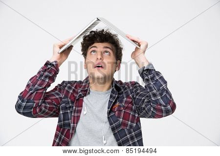 Man holding laptop on his head like roof of hous and looking up