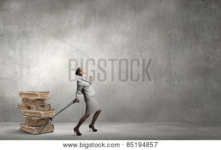Businesswoman with bound hands pulling heavy stack of old books