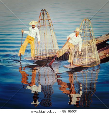 Vintage retro effect filtered hipster style image of Myanmar traditional Burmese fishermen with fishing net at Inle lake in Myanmar famous for their distinctive one legged rowing style