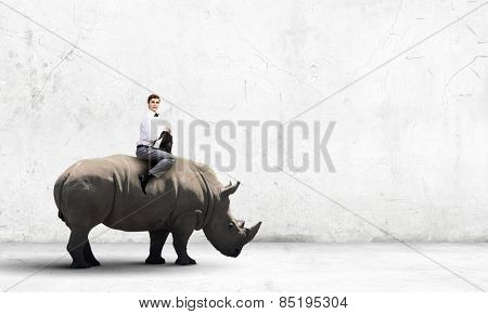 Young fearless businessman with suitcase riding huge rhino