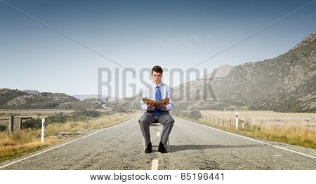 Businessman sitting in chair and reading book