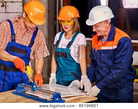 Happy group people builder cutting ceramic tile.