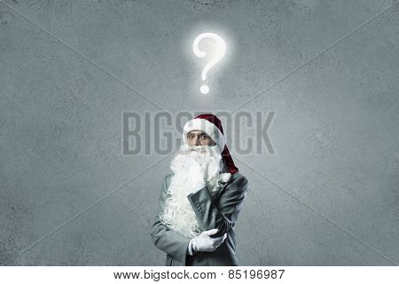 Thoughtful businessman in Santa hat with hand on chin