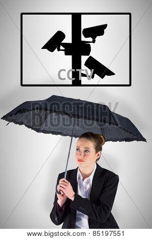 Businesswoman holding a black umbrella against cctv
