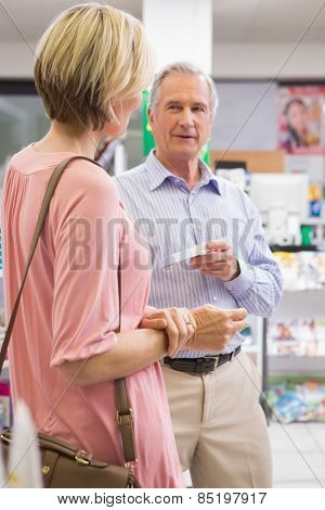 Smiling couple speaking about medication in the pharmacy