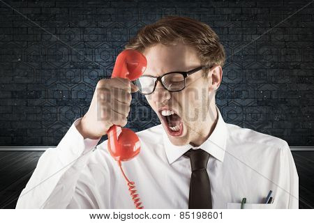 Angry geeky businessman holding telephone against blue background with vignette