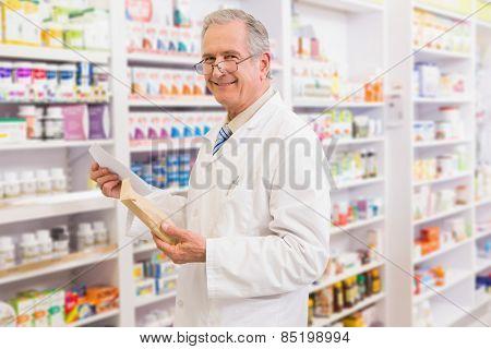 Smiling senior pharmacist holding envelope and prescription in the pharmacy