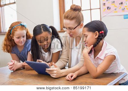 Teacher and pupils looking at tablet computer at the elementary school
